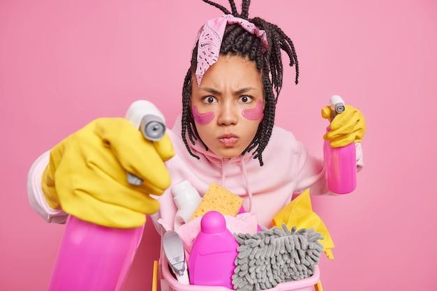 Mann hat dreadlocks posen mit reinigungsmitteln trägt gummihandschuhe hält reinigungsspray oder reinigungsmittel isoliert auf rosa