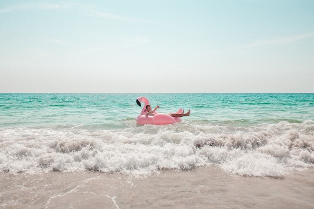 Mann hat spaß auf aufblasbarem poolfloss des rosa flamingos