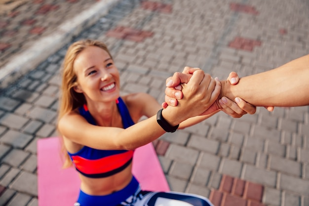 Mann hilft einer schönen sportiven frau, aufzustehen, nachdem er eine sportübung auf teppich getan hat