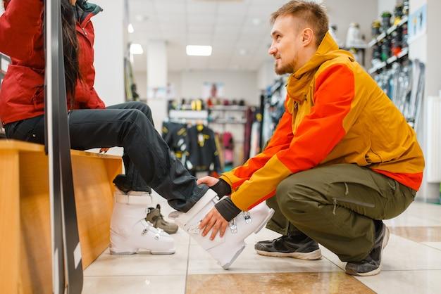 Mann hilft frau beim anprobieren von skischuhen, einkaufen