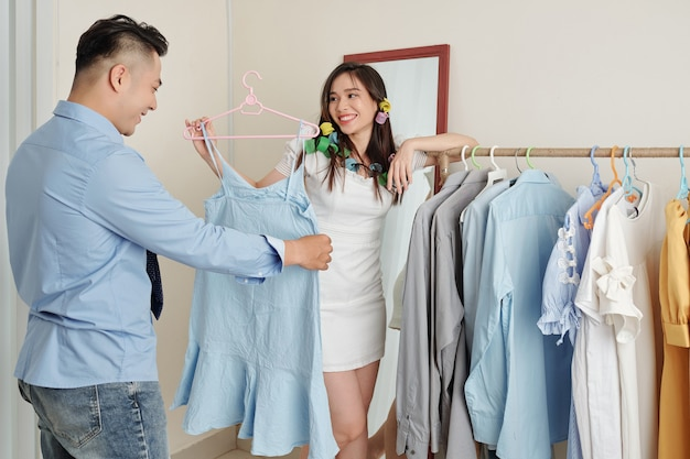 Mann hilft frau, kleid zu wählen
