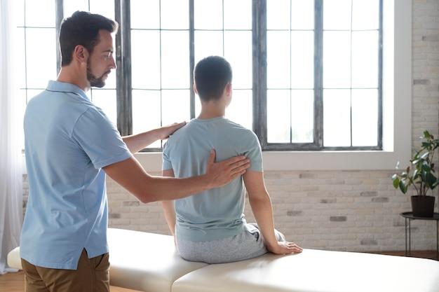 Mann hilft patienten in der physiotherapie mittlerer schuss