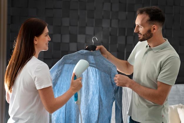 Mann hilft seiner frau beim bügeln eines hemdes