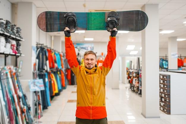 Mann hob das brett zum snowboarden auf, einkaufen im sportgeschäft.