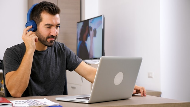 Mann hört musik mit seinen kopfhörern im büro. gute stimmung