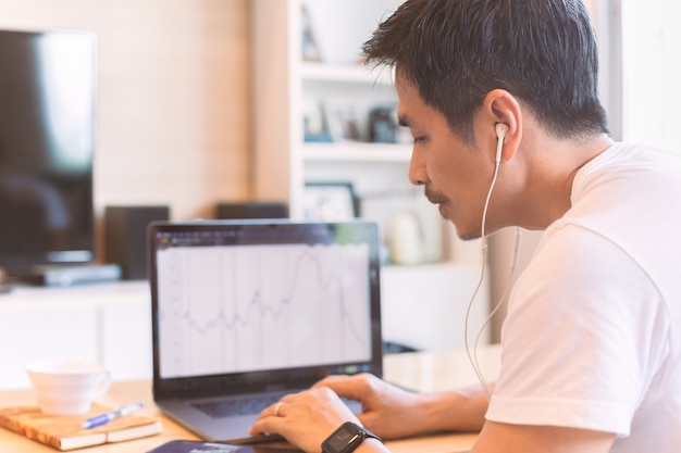 Mann hört musik, während er zu hause am laptop arbeitet