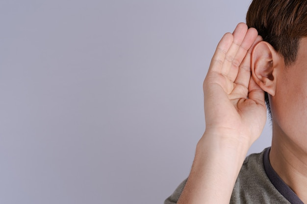 Mann hörverlust oder schwerhörigkeit und seine hand hinter seinem ohr isolieren grauen hintergrund, taubes konzept.