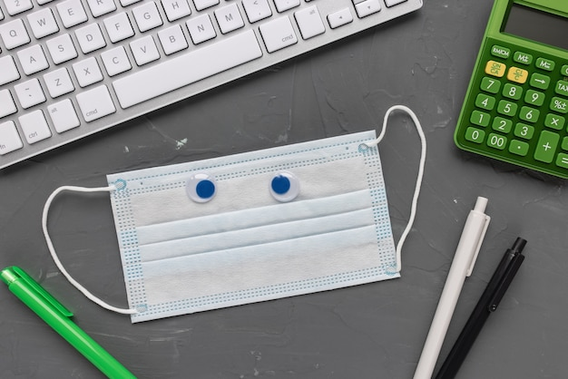 Mann home office. maske, tastatur, taschenrechner, stifte und notizbuch. covid-19 und steuererklärung zeitkonzept