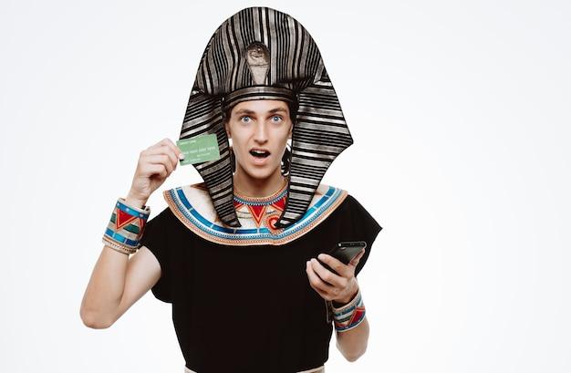 Mann im alten ägyptischen kostüm, das kreditkarte und smartphone auf weiß hält