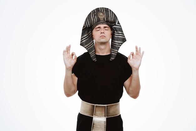 Mann im alten ägyptischen kostüm, das sich entspannt, meditationsgeste mit den fingern auf weiß macht
