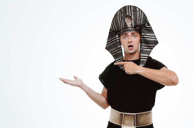 Mann im alten ägyptischen kostüm glücklich und positiv, der mit dem zeigefinger auf seinen arm zeigt, der etwas mit dem arm seiner hand auf weiß präsentiert