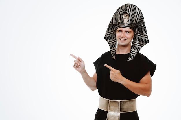 Mann im alten ägyptischen kostüm lächelt selbstbewusst und zeigt mit den zeigefingern zur seite auf weiß