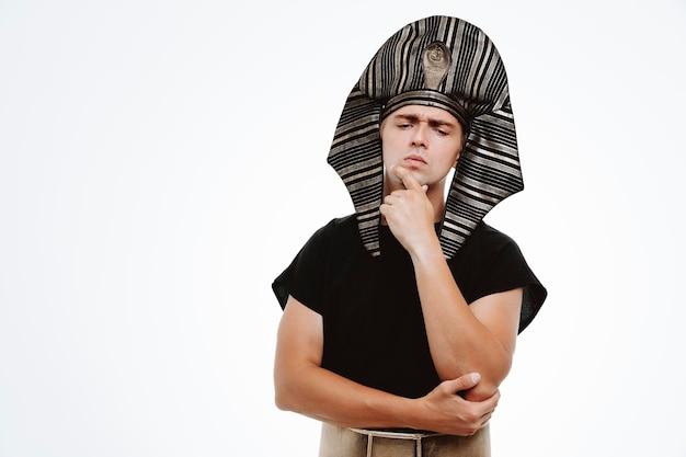 Mann im alten ägyptischen kostüm mit nachdenklichem gesichtsausdruck, der mit der hand am kinn auf weiß denkt