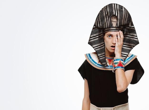 Mann im alten ägyptischen kostüm überrascht, ein auge mit palme auf weiß zu kegeln