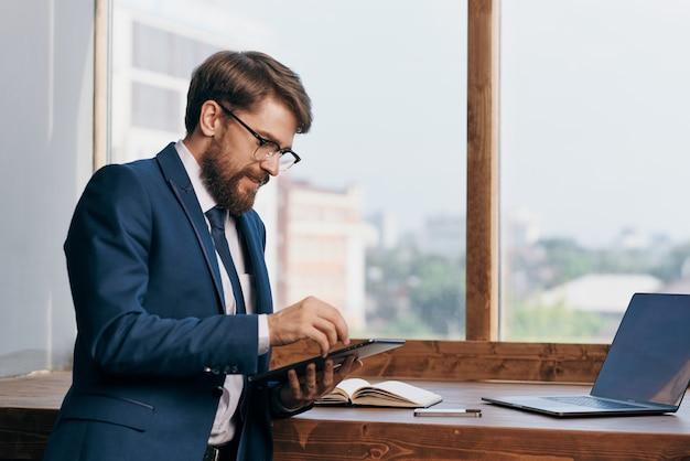 Mann im anzug am fenster mit tablet-technologie. foto in hoher qualität
