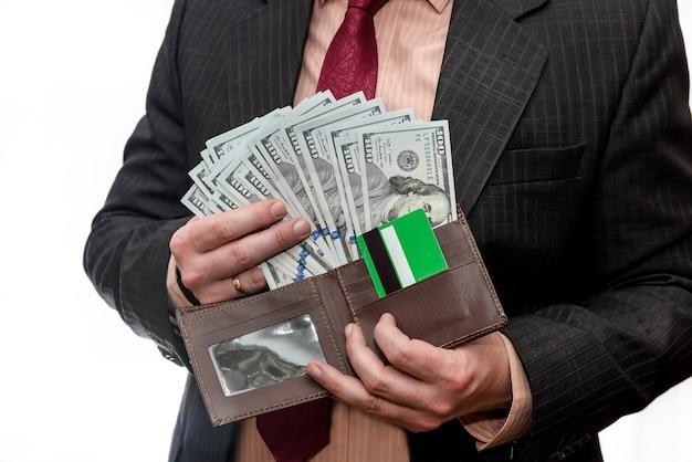 Mann im anzug, der brieftasche mit dollar-banknoten und kreditkarte hält