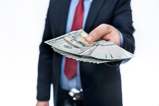 Mann im anzug, der dollarbanknoten nah oben anbietet
