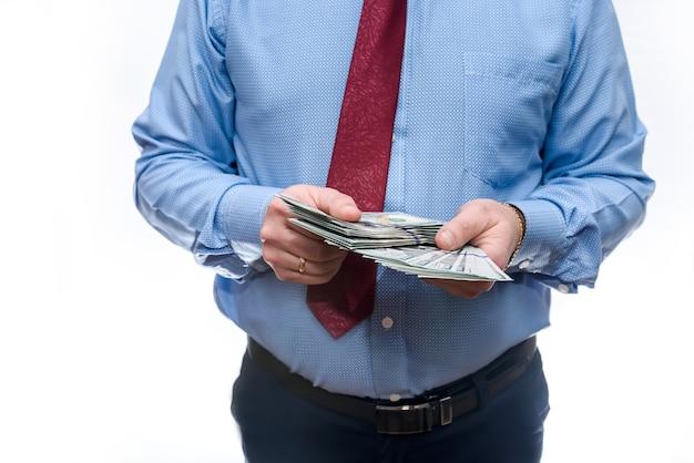 Mann im anzug, der dollarbanknoten nah oben hält