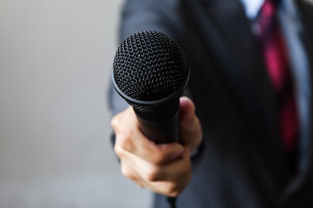 Mann im anzug, der ein mikrofon, formende ereignisse des geschäfts anzeigend hält