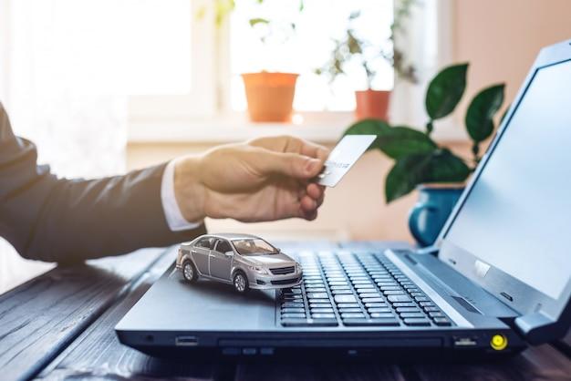 Mann im anzug, der im büro an einem laptop arbeitet und ein auto hält, das mit einer kreditkarte bezahlt