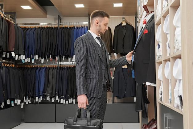 Mann im anzug, der nahe schaufensterpuppe in der boutique wählt.