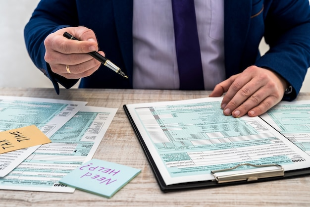 Mann im anzug füllt das us-amerikanische steuerformular 1040 aus. steuerzeit. buchhaltungskonzept