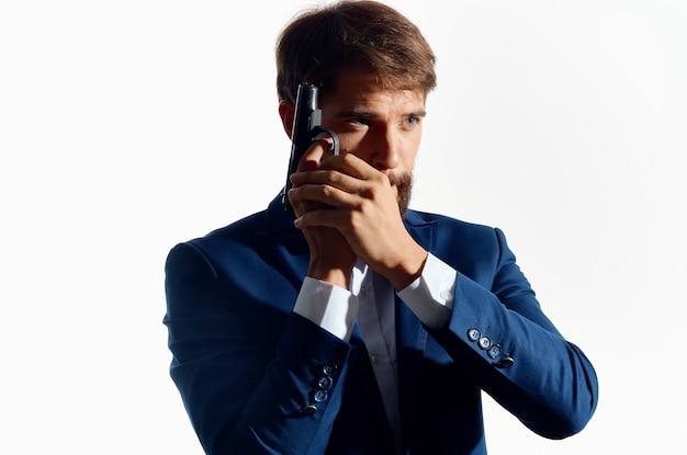 Mann im anzug hält ein waffendetektiv verbrechen isoliert