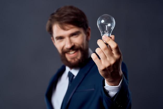 Mann im anzug hält eine lampe idee erfolg innovation. foto in hoher qualität
