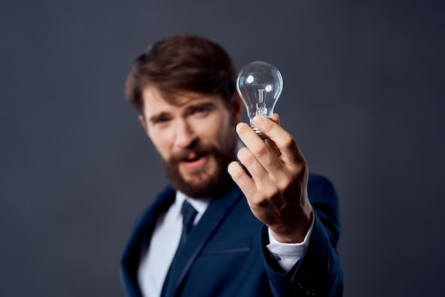 Mann im anzug hält eine lampe idee erfolgsinnovation