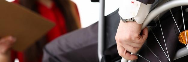 Mann im anzug im rollstuhl kommuniziert mit frauengeschäft