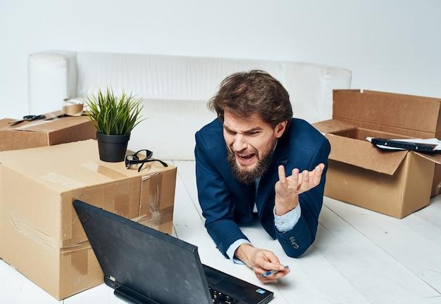 Mann im anzug mit kisten, die laptop-lifestyle-profi bewegen.