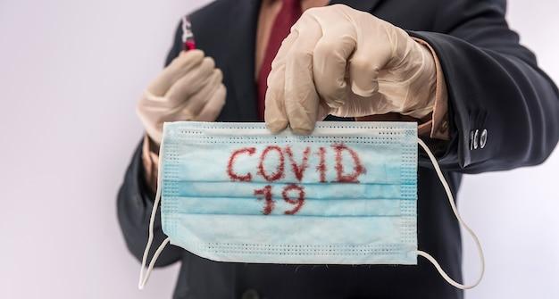 Mann im anzug mit medizinischer schutzmaske mit text covid19. epidemie