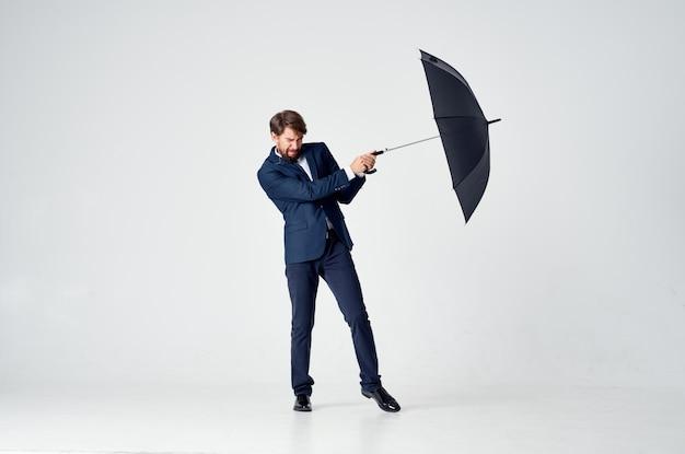 Mann im anzug mit regenschirm schlechtem wetter regen heller hintergrund