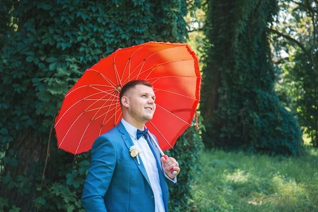 Mann im anzug mit rotem regenschirm im park