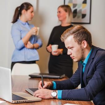 Mann im anzug sitzt am schreibtisch arbeiten