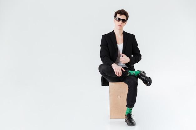 Mann im anzug sitzt auf box