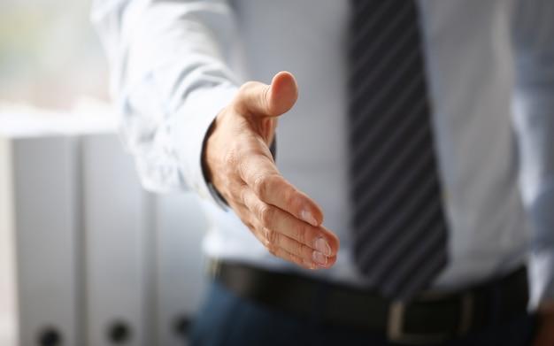 Mann im anzug und bindung geben hand als hallo in der büronahaufnahme