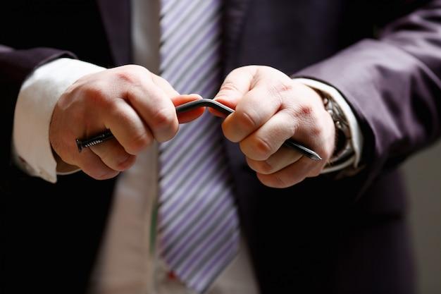 Mann im anzug und in der bindung verbiegen nagel mit armnahaufnahme