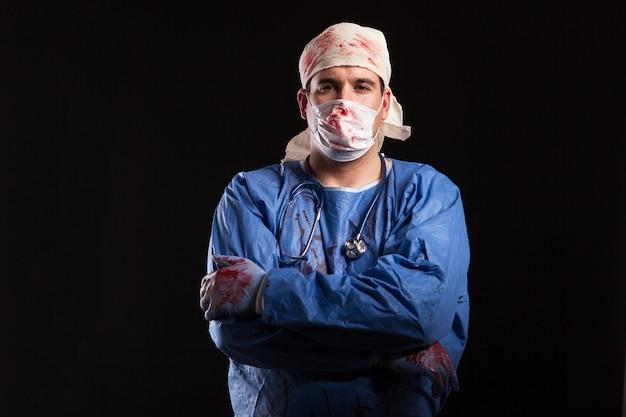 Mann im arztkostüm für halloween, der mit einem bizarren gesicht in die kamera schaut. seltsamer mann mit medizinischem kostüm.