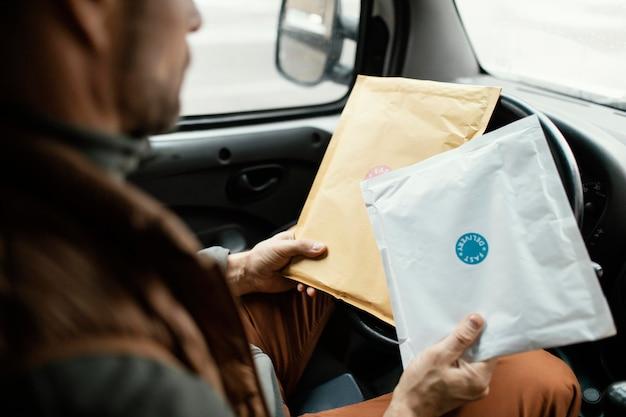 Mann im auto, das paket nahaufnahme liefert