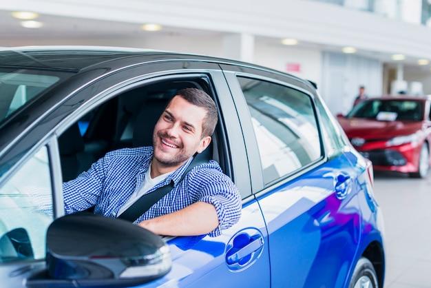 Mann im auto im autohaus
