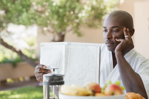 Mann im bademantel, der papier liest und auf terrasse frühstückt