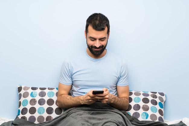 Mann im bett, das eine mitteilung mit dem mobile sendet