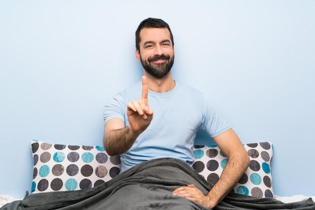 Mann im bett, das einen finger zeigt und anhebt