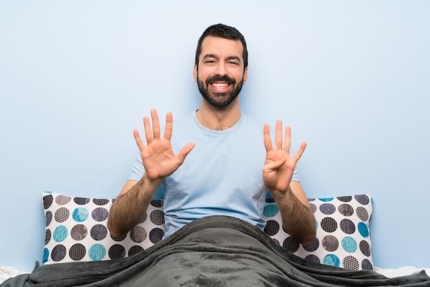 Mann im bett, das neun mit den fingern zählt