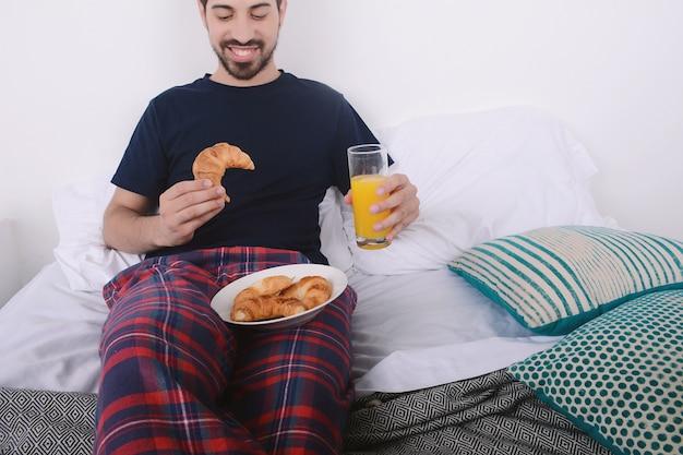 Mann im bett frühstücken.