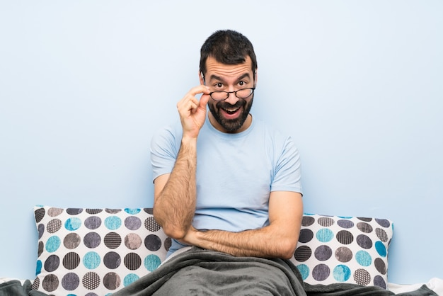 Mann im bett mit brille und überrascht