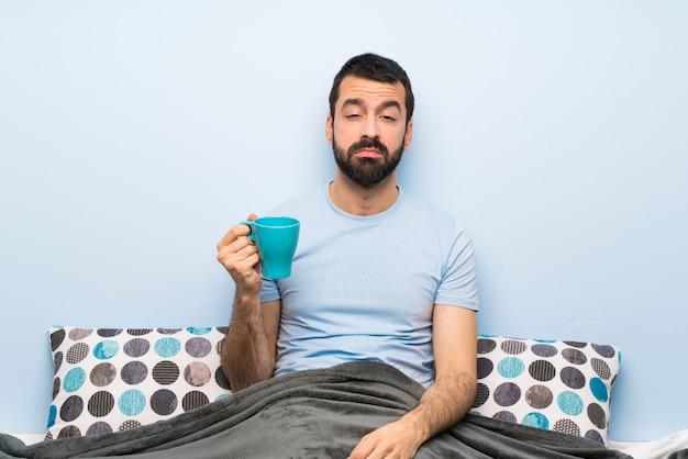 Mann im bett mit dem bart, der einen tasse kaffee hält