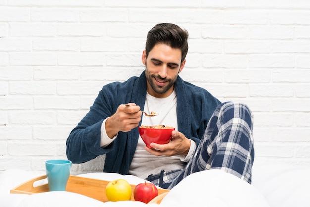 Mann im bett mit hausmantel und frühstücken