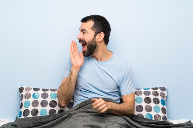 Mann im bett schreit mit weit offenem mund zur seite
